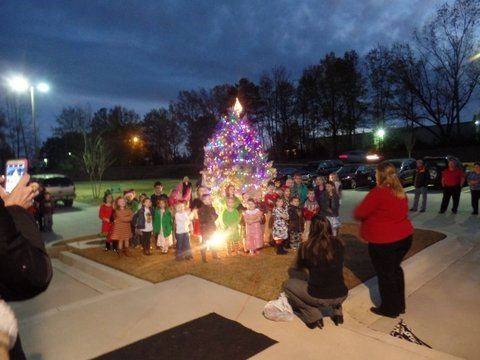 Photo of Children from Chapin Methodist singing around Christmas tree