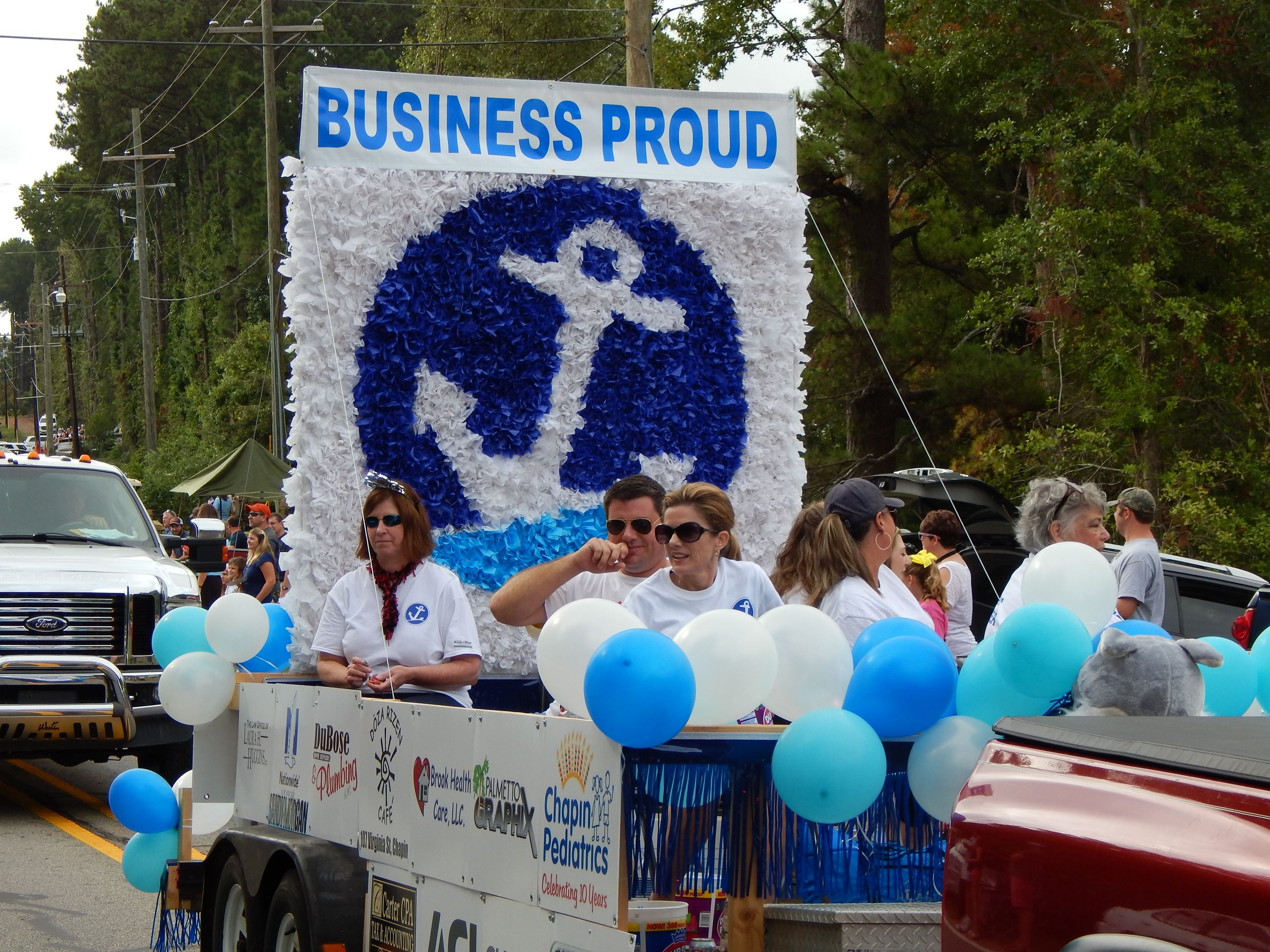 "People riding in a float labeled ""Business Proud."""