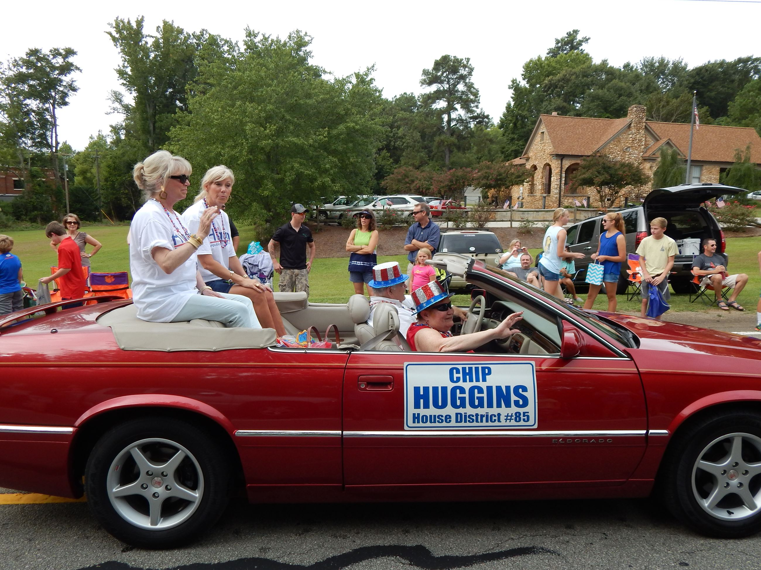 "People riding in a red convertible with the words ""Chip Higgins House District #85."""