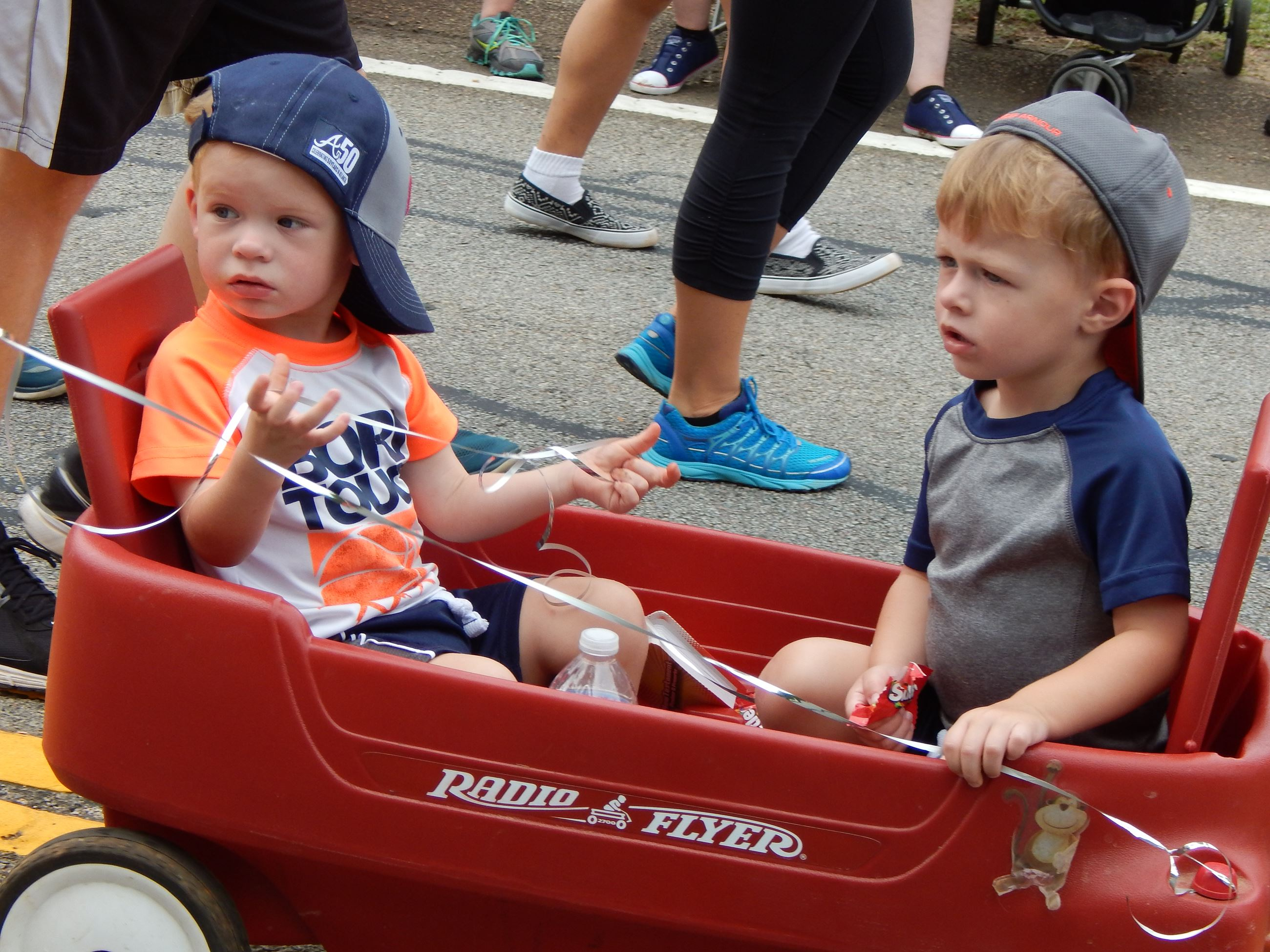 Two young boys in a red wagon.
